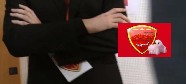 Aningen långsökt men skölden på vaktens id-bricka har samma färger som Ahlgrens vapen. Det kanske är ett sammanträffande, eller så är det inte det!
